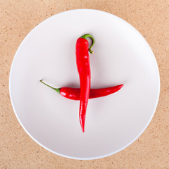 Fresh chili peppers on plate arranged in cross or plus shape