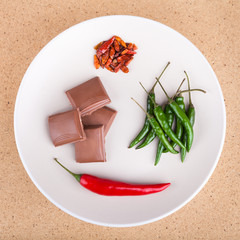 Chili peppers and chocolate on plate