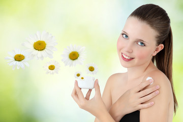 smiling woman with cream lotion on green background and daisies