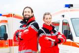 Notartzt und Sanitäter vor Krankenwagen