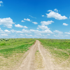 road on hill in green grass and blue sky