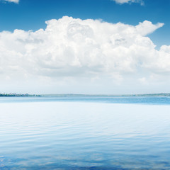 white clouds over blue water