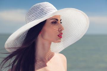 Closeup portrait of woman in big white hat