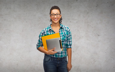 student in eyeglasses with folders and tablet pc