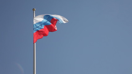 Flag of Russia flutters on a wind against the blue sky