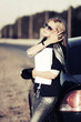 Blond business woman with financial papers at the car