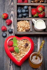 Granola muesli with berries, honey, nuts and milk.