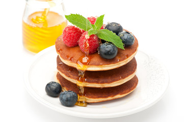 Pancake. Pancakes with raspberries, blueberries and honey
