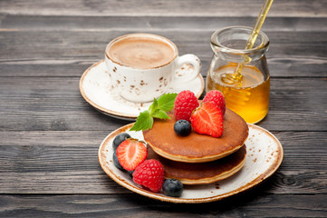 Pancakes, honey, berries and a cup of coffee espresso .