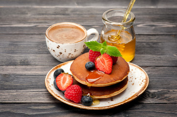 Pancakes, honey, berries and coffee espresso