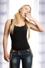 übermüdetet junge Frau gähnt