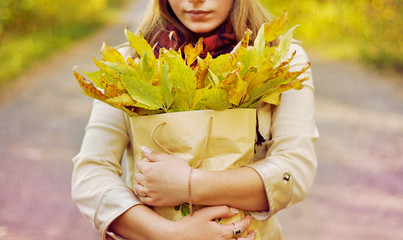 Girl holds a package with leaves