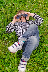 Young boy lying on his back with binoculars