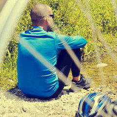 cyclist getting some rest at the riverside with a retro filter e
