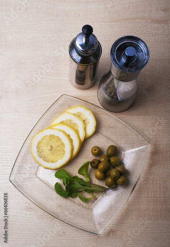 arugula, lemon and olives with spices on the table