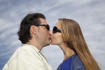 Hombre y mujer besándose con cielo de fondo