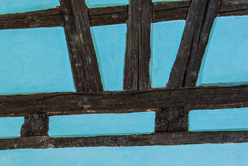 Wall of turquoise half timbered building in France.