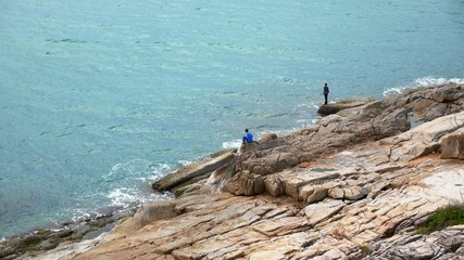 Men Fishing at the bottom of a Mountain. Rocky Seascape.