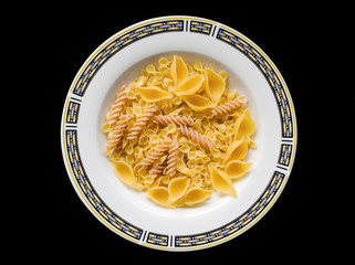 Pasta, plate with an ornament on a black background