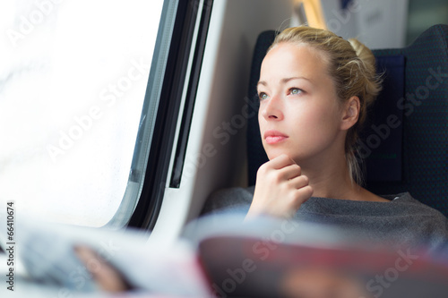 Lady traveling by train. - 66410674