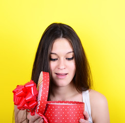 Portrait of happy woman opening gift box against yellow backgrou