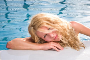 Beautiful young woman at summer swimming pool