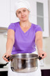 Woman holding out a metal saucepan
