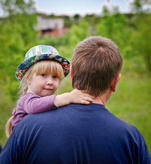 Cute little blond girl being carried by her father