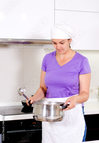 Female cook smelling her recipe in the pot