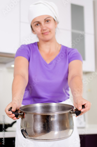 Woman holding out a metal saucepan