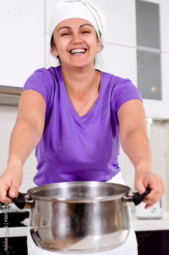 Laughing attractive cook with a big pot