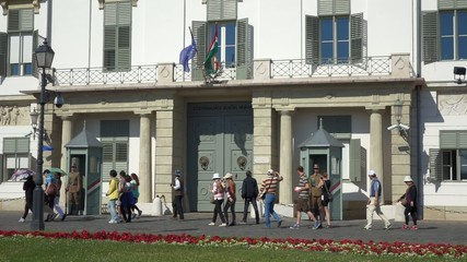 Tourists walk in front of the Sandor Palace