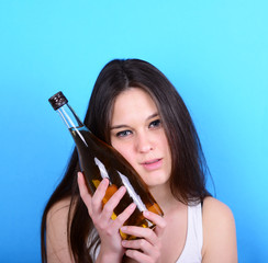 Portrait of young female having hangover with bottle pf alcohol