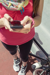 Sportive woman with fixie bike looking smartphone