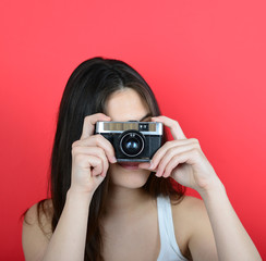 Portrait of young female holding vintage camera against red back