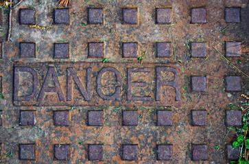 Old manhole with the word danger