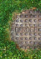 Sewer manhole with grass and word danger