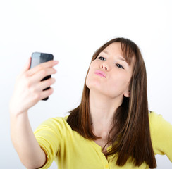 Beautiful woman taking selfies against white background