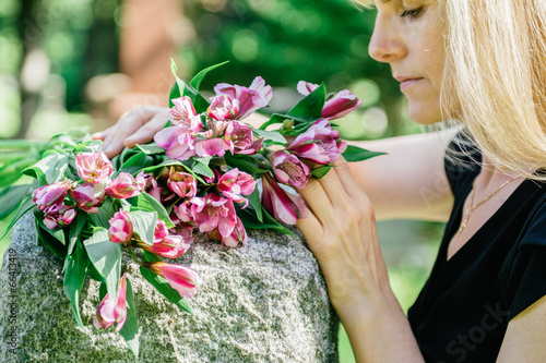 Woman Grieving at Grave - 66413419