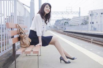 駅のベンチに座る女性
