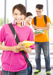 pretty young student holding books and earphone with classmates