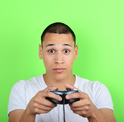Portrait of young man holding game controller and playing games