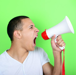 Portrait of young man shouting with a megaphone against green ba