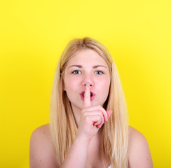 Portrait of girl with gesture for silence against yellow backgro