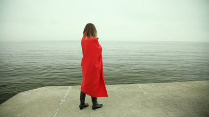 Lonely girl in red blanket on the pier