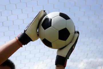 goalkeeper's hands reaching foot ball