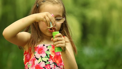 Girl child kid blowing a soap bubbles outdoor