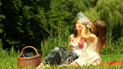 Picnic. Mother with daughter relaxing. Child drinking water.