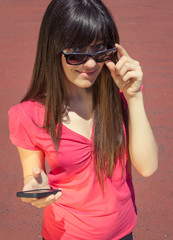 Young woman with phone looking over her sunglasses