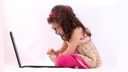 Little girl playing with laptop against white background